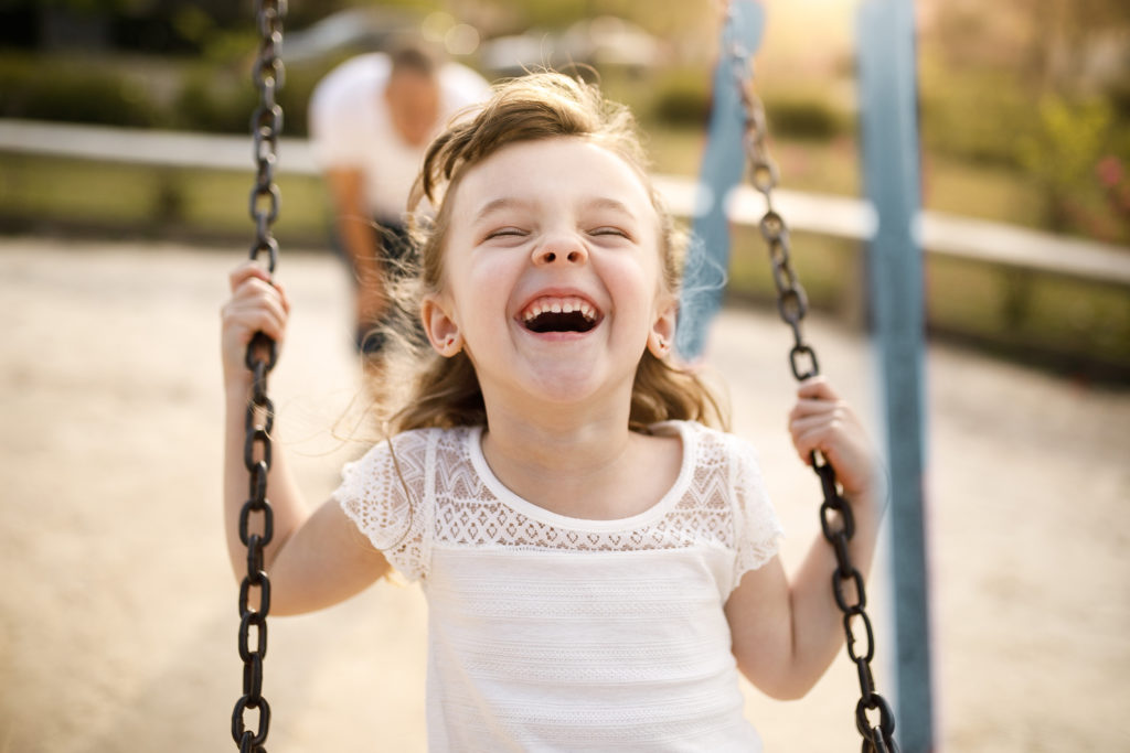 Picture of a child laughing on a swing