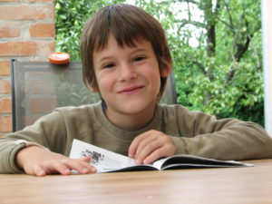 Picture of a smiling primary school-age child with book, smiling at camera
